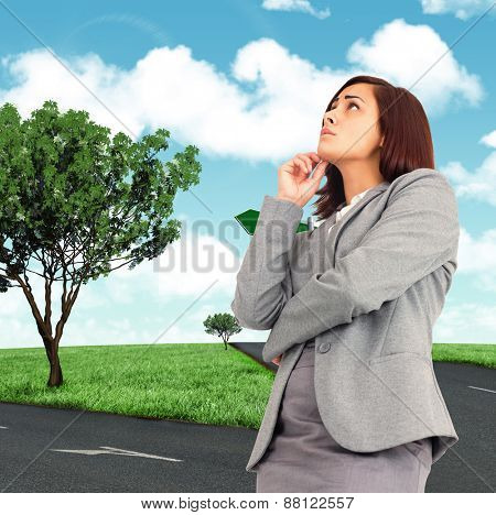 Worried businesswoman against road leading out to the horizon
