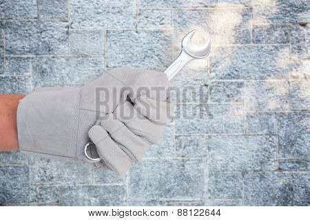 Mechanic holding spanners on white background against grey