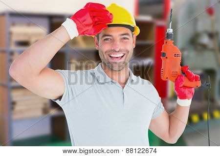 Smiling manual worker holding drill machine against workshop