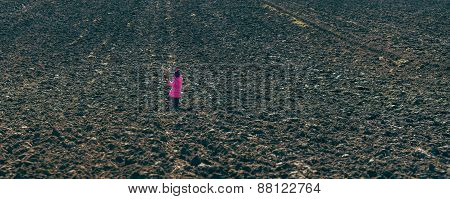 Girl Standing In The Midst Of Plowed Fields