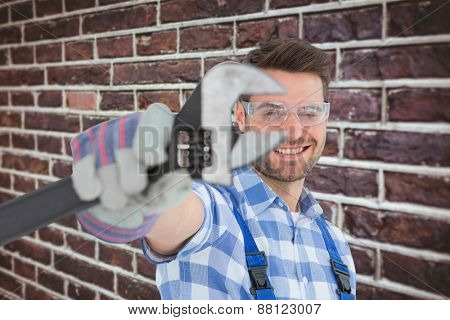 Handyman wearing protective glasses while holding wrench against red brick wall