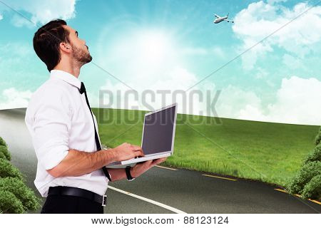 Sophisticated businessman standing using a laptop against road leading out to the horizon