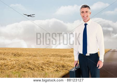 Smiling businessman wearing a headphone against road leading out to the horizon
