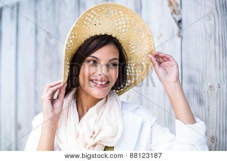Smiling beautiful brunette wearing straw hat on wooden plank background