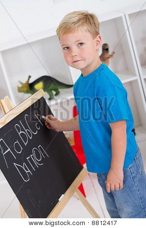 cute boy writing on chalkboard