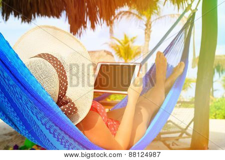 young woman relaxing in hammockwith touch pad at the sea