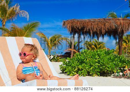 cute little girl drinking juice on tropical beach