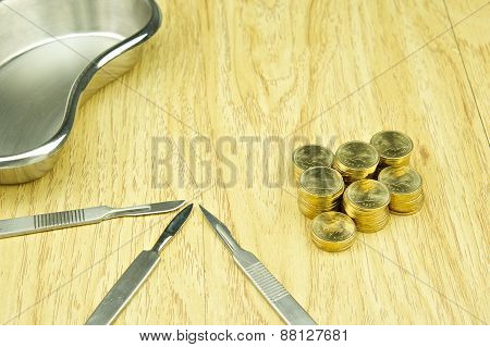 Silver Scalpel And Pile Of Gold Coins With Emesis Basin