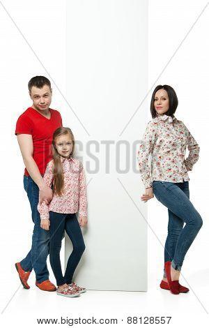 Happy family standing behind billboard