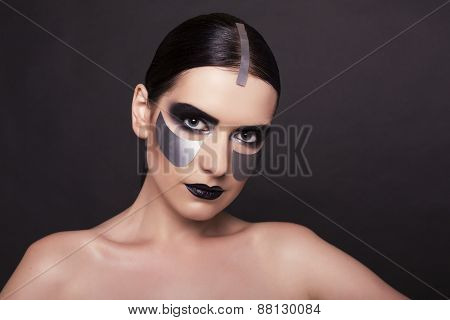 Woman With Dark  Hair And Metallic Extraordinary Makeup