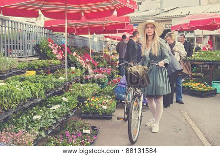 ZAGREB, CROATIA - MARCH 4, 2014: Attractive blonde girl with straw hat and bike on Dolac Market. Dolac has  been the city's major trading place since 1926.