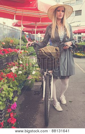 Attractive blonde girl with straw hat and bike on Marketplace. Post processed with vintage filter.