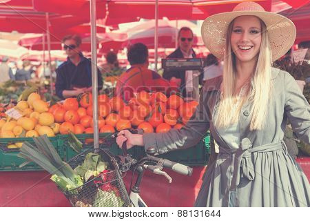Attractive blonde woman with straw hat and bike on Marketplace. Post processed with vintage filter.