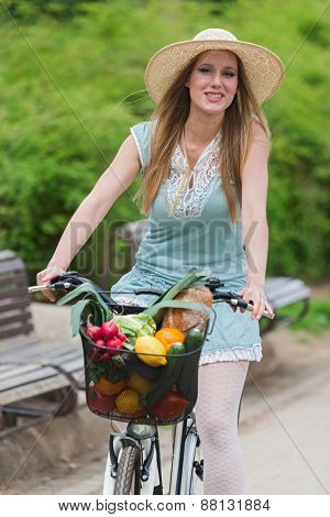 Attractive blonde woman with straw hat riding a bike with basket full of groceries.