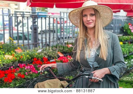 Attractive blonde girl with straw hat and bike on Marketplace.