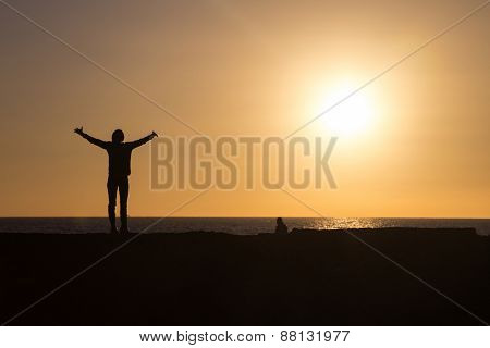 Silhouette of woman raising hands to sun at sunset.