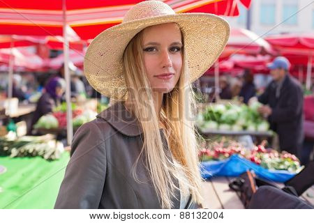 Portrait of attractive blonde girl with straw hat on Marketplace.