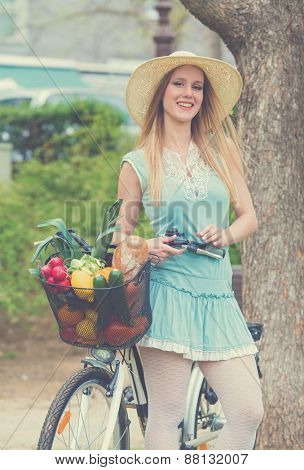 Attractive blonde woman with straw hat standing in the park and posing next to bike with basket full of groceries. Post processed with vintage filter.