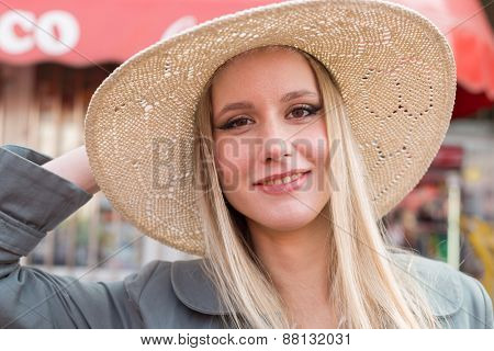 Portrait of attractive blonde woman with straw hat on Marketplace.