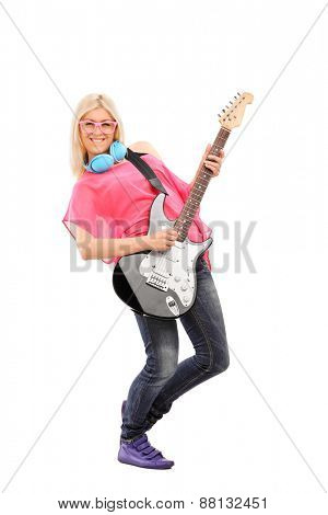 Full length portrait of a beautiful blond woman playing an electric guitar and wearing blue headphones around her neck isolated on white background