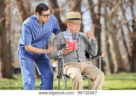 Young male doctor comforting a sad senior man seated in a wheelchair in a park