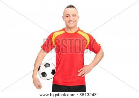 Football player in a red and yellow shirt holding a ball, smiling and looking at the camera isolated on white background