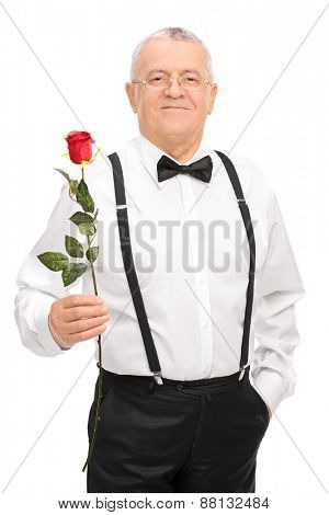 Vertical shot of an elegant senior gentleman holding a red rose, smiling and looking at the camera isolated on white background