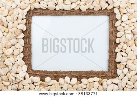 Frame Made Of Burlap With The Line And Pumpkin Seeds Lies White Background