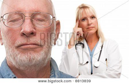 Concerned Senior Man And Female Doctor Behind