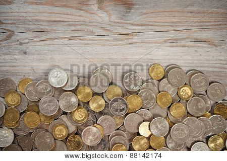 Top view coins on old wooden desk with copy space on top.
