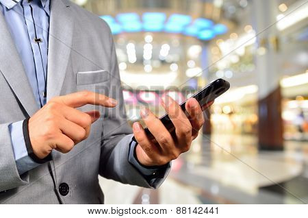 Handsome Young Man In Shopping Mall Using Mobile Tablet.