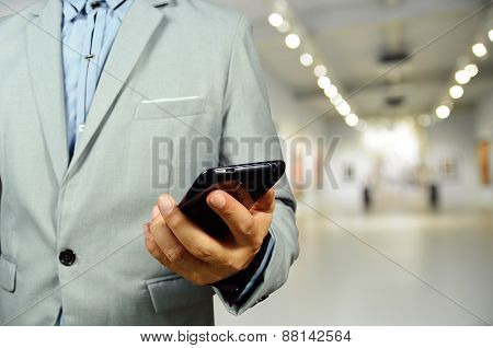 Business Man Using Mobile Phone In The Art Gallery Hall