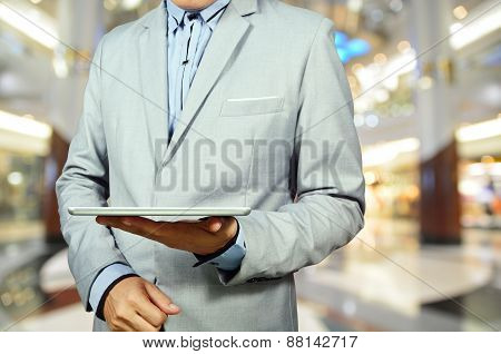 Handsome Young Man In Shopping Mall Using Mobile Tablet Pc.