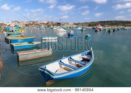 MARSAXLOKK, MALTA - JANUARY 11, 2015: Old traditional wooden fishing boats in the harbour on a sunny day.
