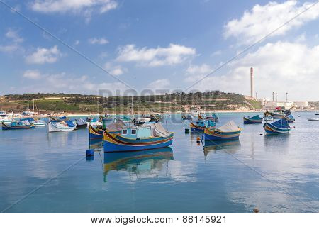MARSAXLOKK, MALTA - JANUARY 11, 2015: Luzzus, traditional fishing eyed boats in the harbour.