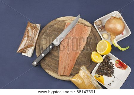 Preparation of frozen salmon, homemade dressing, salmon on a wooden chopping board