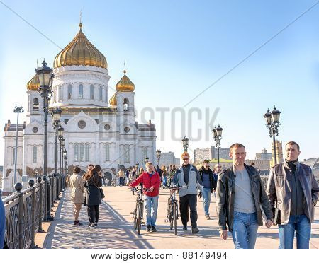 Moscow, Russia - April 11, 2015: People Walking On The Patriarch Bridge Against The Cathedral Of Chr