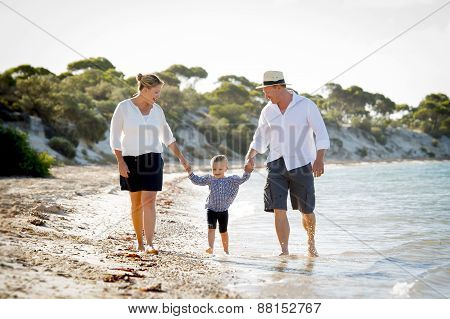 Young Happy Mother And Father Walking On Beach In Family Vacation Concept