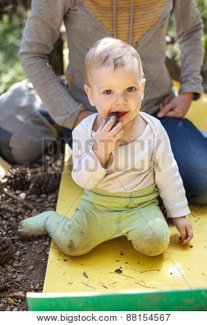 Little boy biting a cone, mother behind the boy