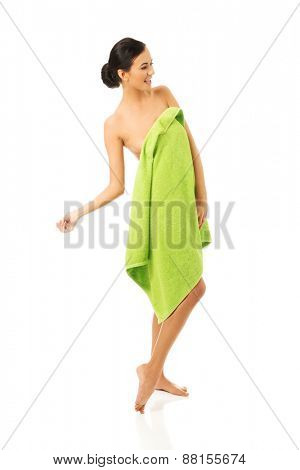 Full length woman standing wrapped in towel.