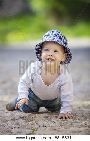Cute little boy crawling on stone paved sidewalk