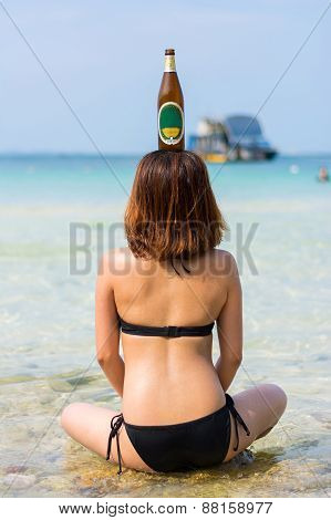 Sexy Asian Thai Girl Is Sitting In The Salt Water On The Seashore With Bottle On Her Head