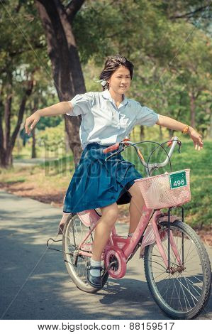 Thai Schoolgirl Playing Risky On A Bicycle, In The Park In Vintage Theme.