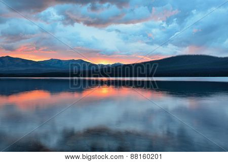 Beautiful Red Sunset Into The Mountains And Mcdonald Lake In Glacier National Park