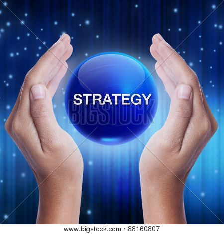 Hand showing blue crystal ball with strategy word.