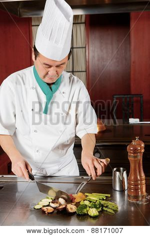 Cook prepares fried vegetable dish