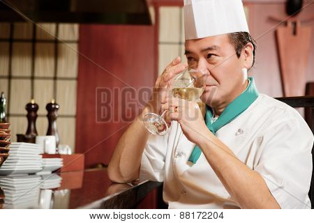Cook has a drink in restaurant kitchen