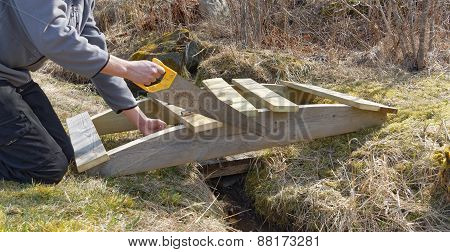 Man Building A Small Wooden Curved Bridge