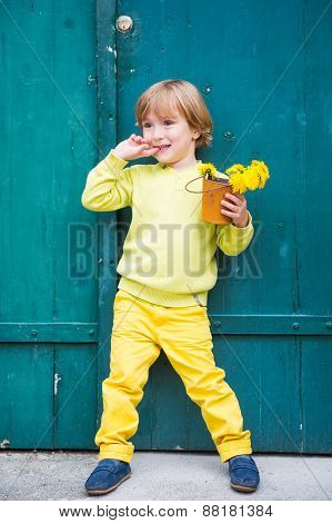 Outdoor portrait of a cute little boy, wearing yellow pullover and trousers