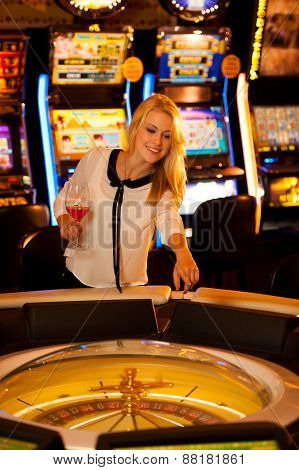 Young Blond Woman Playing Roulette In Casino And Winning